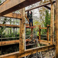 person working on a self build oak frame