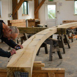Working on an oak beam with hand tools