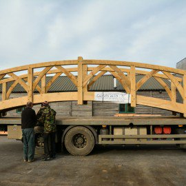 side view of oak garden bridge being loaded on to a truck