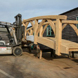 oak garden bridge being moved with a forklift truck