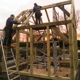 carpenters fitting roof beans to new oak framed garden room