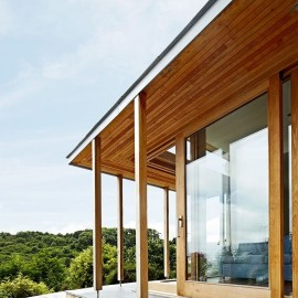 Glass Sliding Door on Loggia in Contemporary Chestnut Glulam Framed Extension on House in Cornwall by Carpenter Oak Ltd Devon