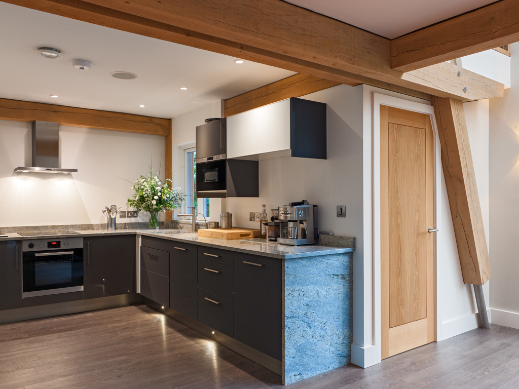 Oak framed kitchen inside a state of the art eco house - timber frame houses by Carpenter Oak Ltd