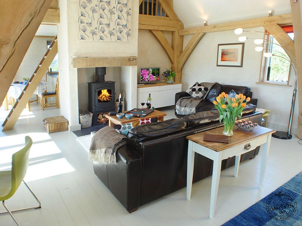 Living Room with Oak Frame Sling Brace Truss and Woodburner in Self Build Timber House in Cornwall